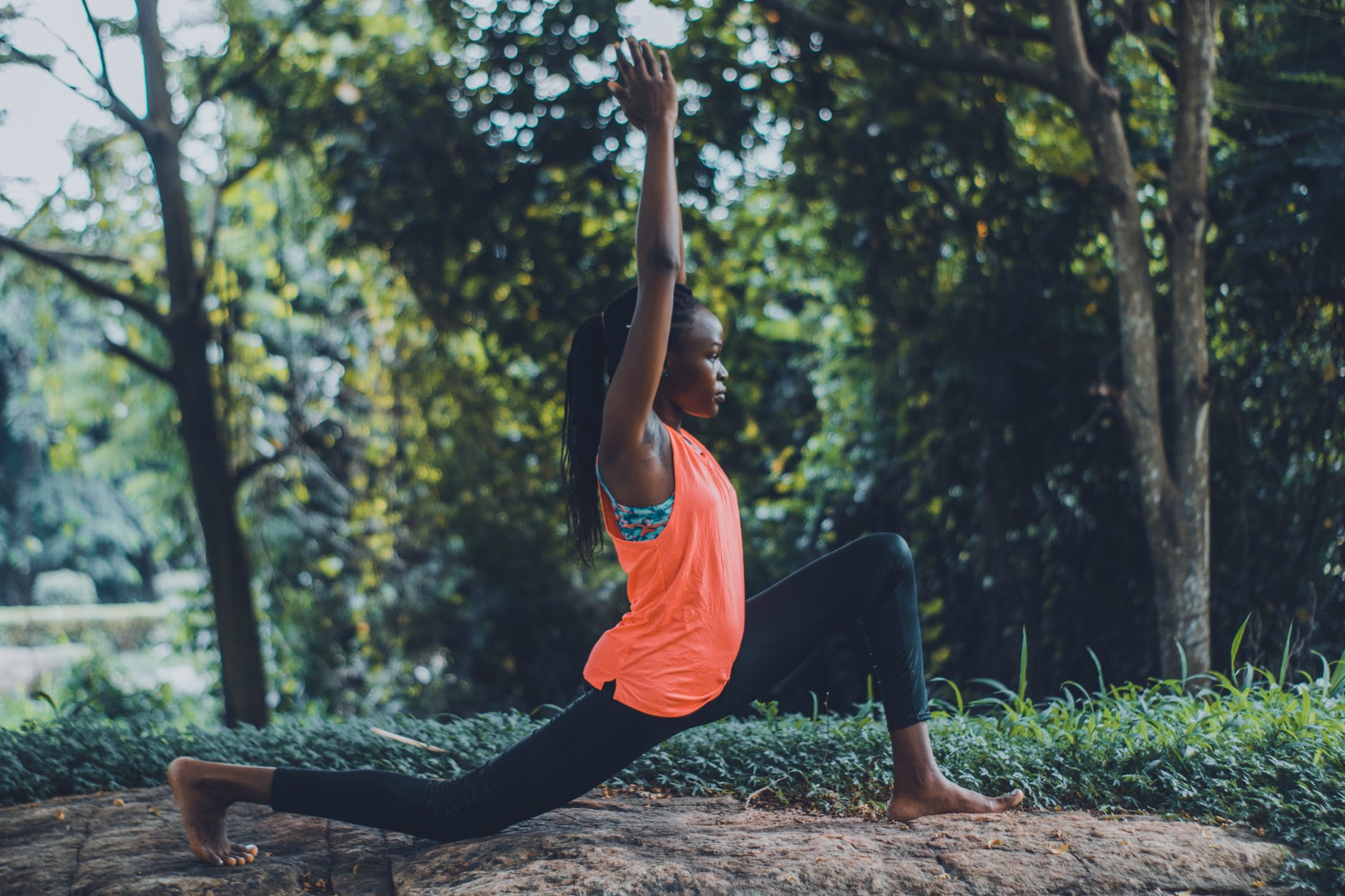photo of woman in orange tank top and black pants striking a yoga pose outdoors