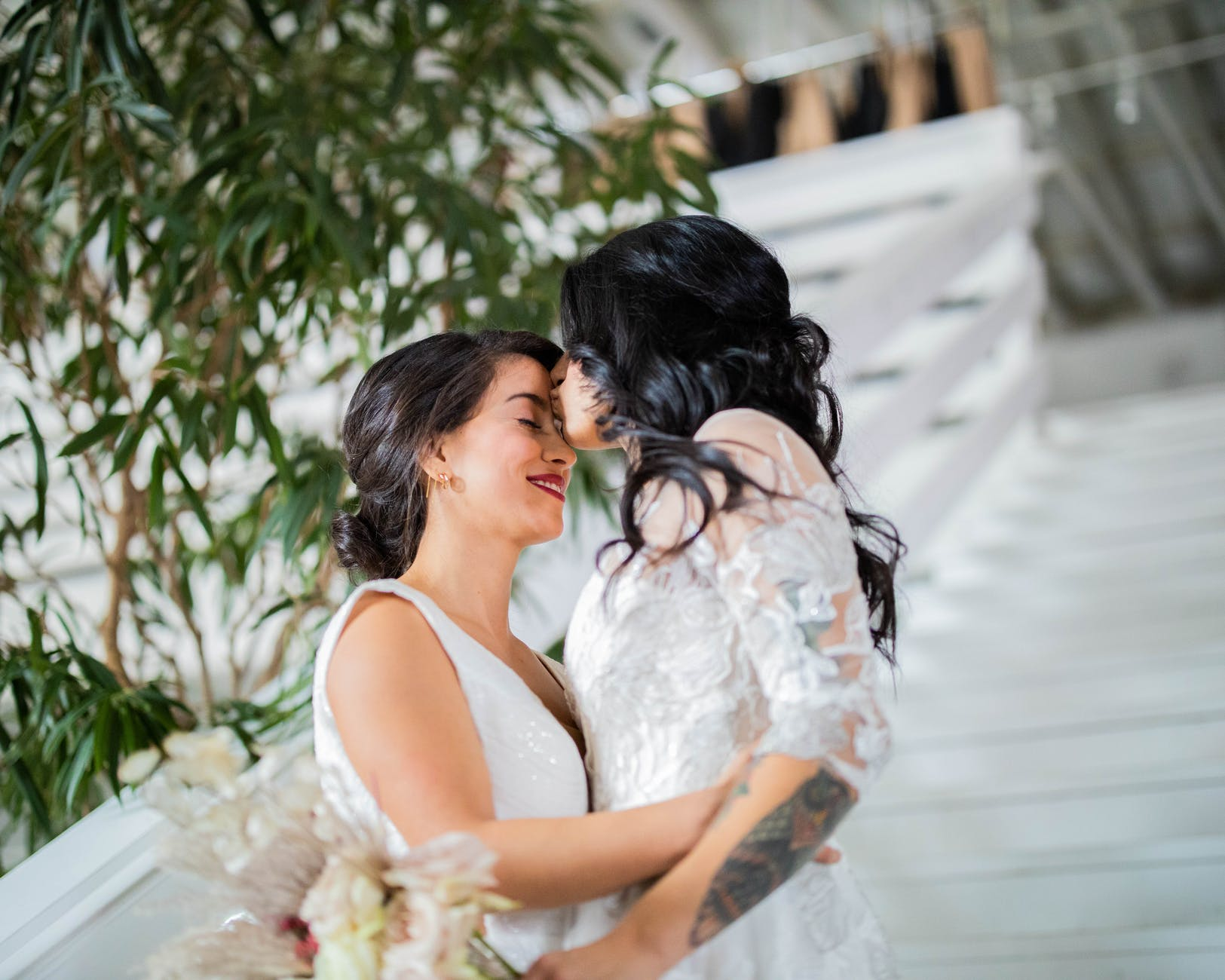 woman in white floral dress kissing woman in white dress