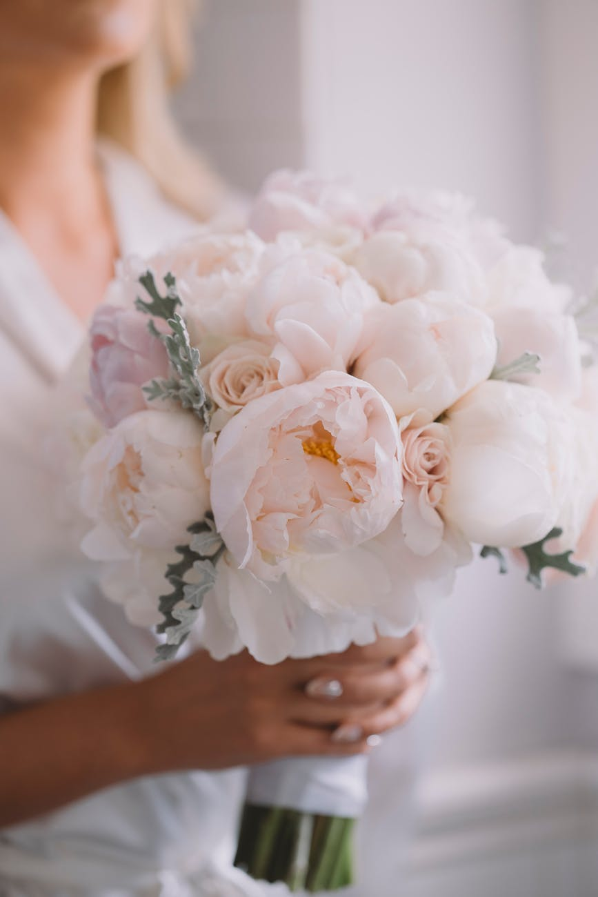 crop bride with blooming peony bouquet on wedding day