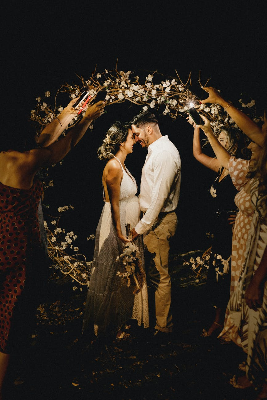 cheerful couple kissing near guests holding decorative wreath at wedding