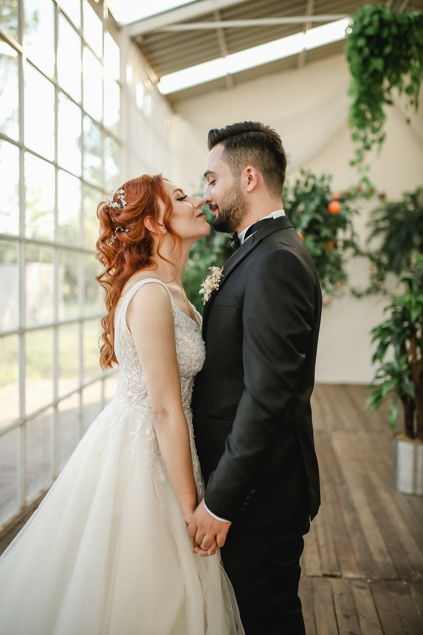 the bride and groom holding hands kissing